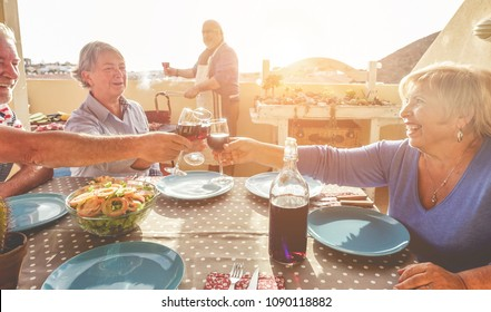 Group of happy senior friends cheering at barbecue meal in terrace outdoor - Mature old people dining and drinking wine at patio bbq lunch - Focus on glasses - Joyful elderly lifestyle concept