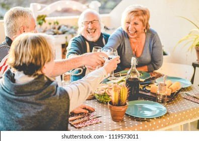 Group of happy senior friends cheering at barbecue meal in terrace outdoor - Mature old people drinking wine at patio bbq dinner - Main focus on left hands glasses - Joyful elderly lifestyle concept