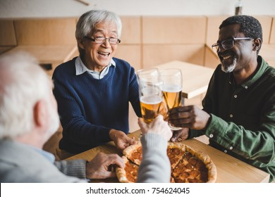 group of happy senior friends clinking glasses of beer in bar with pizza on table
