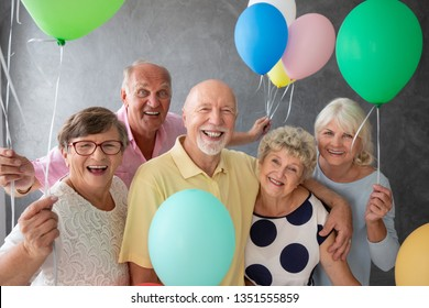 Group of happy, senior friends holding colorful balloons while posing for a photo at a party