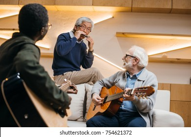 group of happy senior friends playing music with guitars and harmonica