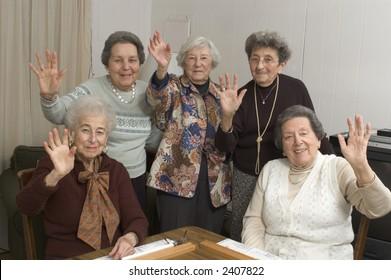 group of happy senior women playing mah-jong with friends waving hello