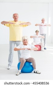 Group of happy seniors during physical exercises, light interior