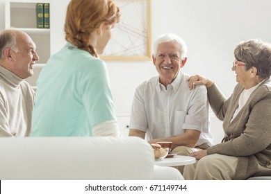 Group of happy seniors sitting and talking with young nurse