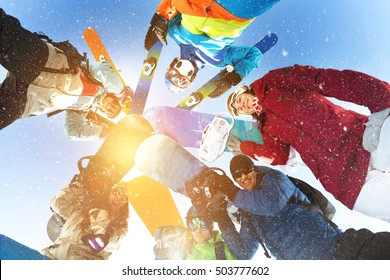 Group of happy skiers and snowboarders stands in circle and smiling