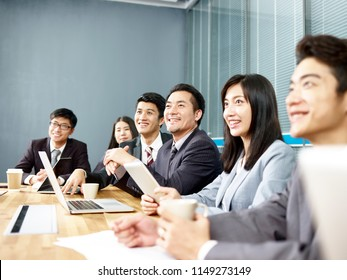 group of happy smiling asian corporate business people listening to presentation in office meeting room