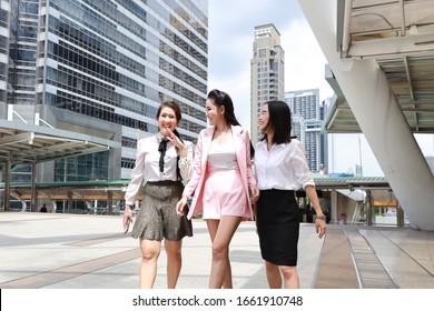 group of happy smiling asian young businesswoman in formal wear, they arguing and discussing startup project while walking during lunch break outdoor with urban view background