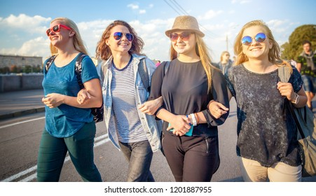 Group of happy smiling carefree young stylish girl go for a walk together on the background of the city, millenial concept, youth and students, tourism and holidays
