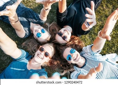 Group of happy smiling carefree young stylish girls  lying on the grass in the park, millenial concept, youth and students, tourism and holidays