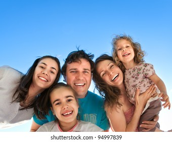 Group of happy smiling friends: man, women and kids having fun outdoors against blue sky background. Summer vacations concept