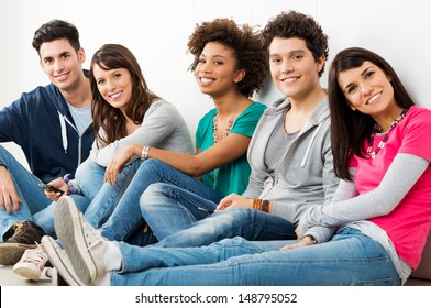 Group Of Happy Smiling Friends Sitting In A Row indoor
