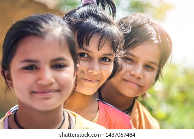 Group of happy smiling Indian little village girls standing in front of mud house.