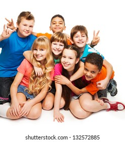 Group of happy smiling kids sitting together and playing - boys and girls black and Caucasian, hugging together
