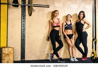 Group of happy smiling muscular sports fitness female and male adults people standing together as good friends in gym with sport equipment in background after a difficult workout session copyspace