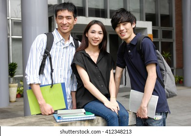 A group of Happy smiling students standing together with books at a campus