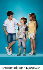The group of happy smiling teen girl and boys on a blue color studio background. Stylish teen boys and girl posing at studio. Casual style and kids fashion concept. Children's fasion concept - Image