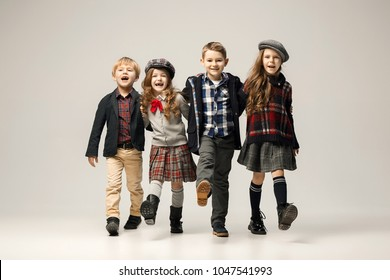 The group of happy smiling teen girls and boys on a pastel studio background. Stylish young teen girls posing at studio. Classic autumn style. Teen and kids fashion concept. children's fasion concept