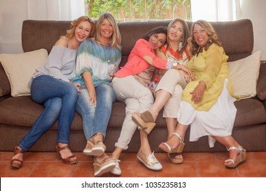 group of happy smiling women sitting on sofa