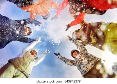 Group of happy snowboarders and skiers having fun and throwing up snow