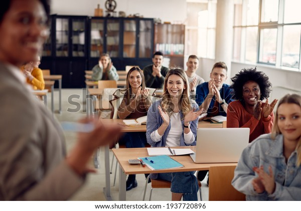 Group of happy students applauding to their lecturer while attending class at the university classroom.