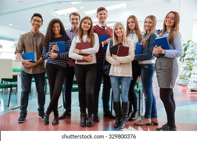 Group of a happy students standing in classroom together and looking at camera