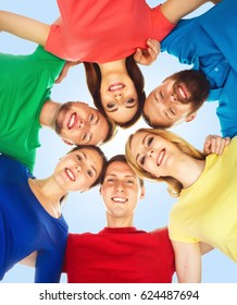 Group of happy students standing together and looking at camera over blue background.  School, university, education, concept.