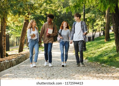 Group of happy students walking at the campus outdoors, talking