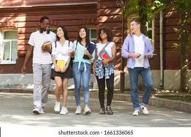 Group of happy students walking in university campus, chatting and laughing during break, copy space