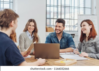 Group of happy successful businesspeople having a team meeting or brainstorming session grouped around an office table