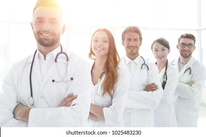 Group of happy successful doctors standing in a row in the hospi