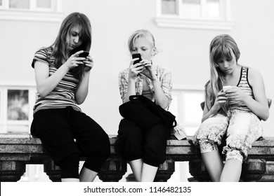 Group of happy teen girls using smart phones against a school building