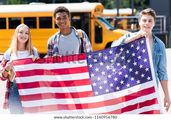 group of happy teen students holding usa flag in front of school bus