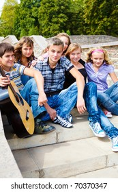 Group of happy teenage friends sitting on stairs with guitar