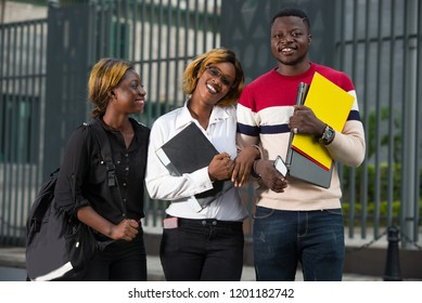 Group of happy teenage students in casual outfit with notebook outside campus