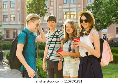 Group of happy teenagers 13, 14 years walking along the city street, friends greet each other at a meeting. Friendship and people concept