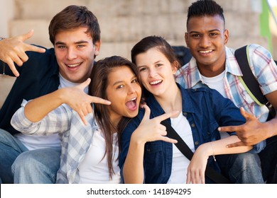 group of happy teenagers giving cool hand signs
