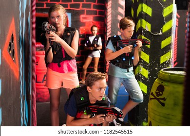Group of happy teenagers with laser guns having fun on dark lasertag arena