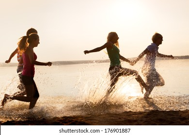 Group of happy teenagers running through the water at the beach