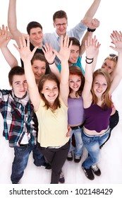 Group of happy teenagers, smiling and looking at camera with hands arms up, top view