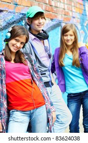 Group of happy teens by painted wall looking at camera