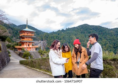 Group of happy tourism gossip and laughing at Sanjunoto Pagoda with background of Nachi waterfalls at Kumano World heritage , wakayama , Japan. Group of young people looking at photo look so happy