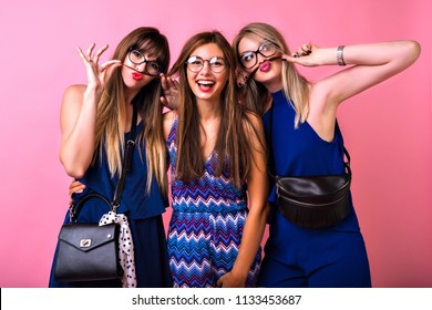 Group of happy tree best friends woman's going crazy together, making funny face and imitating mustache, nave color matching clothes, party time, pink background.
