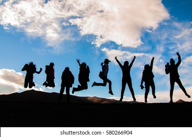 Group of happy women playing on meadow,mountain and blue sky background, summertime.Backpackers silhouette