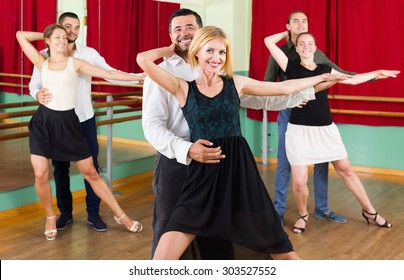 Group of happy young adults having tango class at dance studio. Selective focus