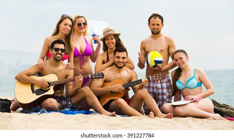 Group of happy young adults relaxing on sand at beach with guitar. Selective focus