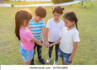 Group of happy young Asian children pile or stack hands togerther outside in city park playground in summer day. Children and recreation concept. Multi-ethnic children group, outdoor.