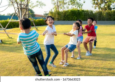 Group of happy young Asian children playing tug of war or pull rope together outside in city park playground in summer day. Children and recreation concept. Multi-ethnic children group, outdoor.