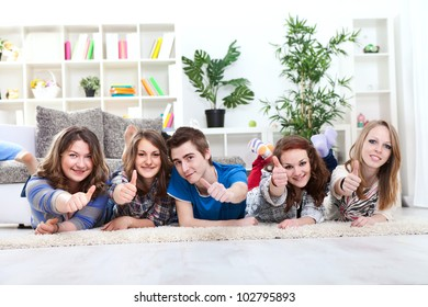 Group of happy young boy and girls lying down and holding thumbs up in the air