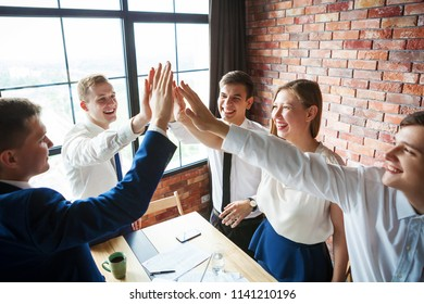 Group of happy young business team celebrating and high fiving each other.