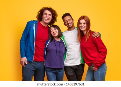 Group of happy young diverse people in bright colorful outfits smiling for camera and embracing each other against yellow background